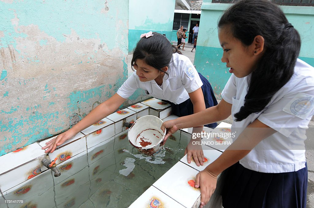 Schoolgirls wash a drinking fountain at their school as part of a Health Ministry campaign focused on mosquito control in order to combat dengue fever, a disease caused by four strains of virus that are spread by the mosquito Aedes aegypti, in Tegucigalpa on July 8, 2013. Authorities have issued dengue alerts in four nations across Central America, where alarm is rising as the mosquito-borne disease has infected 30,000 people and killed 17 this year alone. The illness can be fatal, developing into hemorrhagic fever, which can lead to shock and internal bleeding. AFP PHOTO / Orlando SIERRA