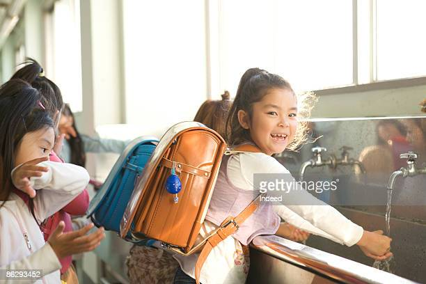 Schoolgirls washing hands, smiling