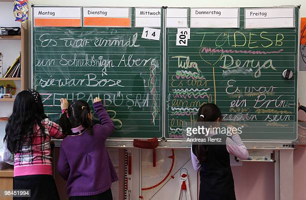 Schoolgirls write on a black board during a lesson at the privat TUEDESB primary school on April 14 2010 in Berlin Germany Turkish Prime Minister...