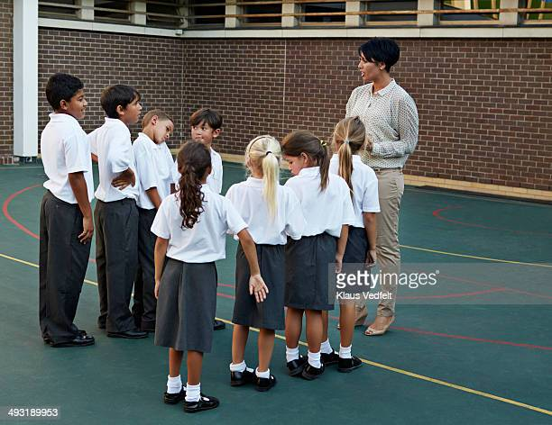 Schoolkids lining up in front of teacher