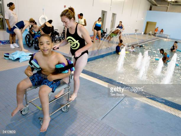 Schwab Rehabilitation Hospital occupational therapist Tricia Watson prepares to bring camper Clarence Council into the pool during activities at a...