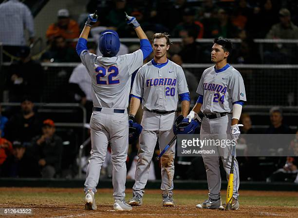 Schwarz is congratulated by Peter Alonso and Jeremy Vasquez of the Florida Gators after hitting a solo home run against the Miami Hurricanes on...