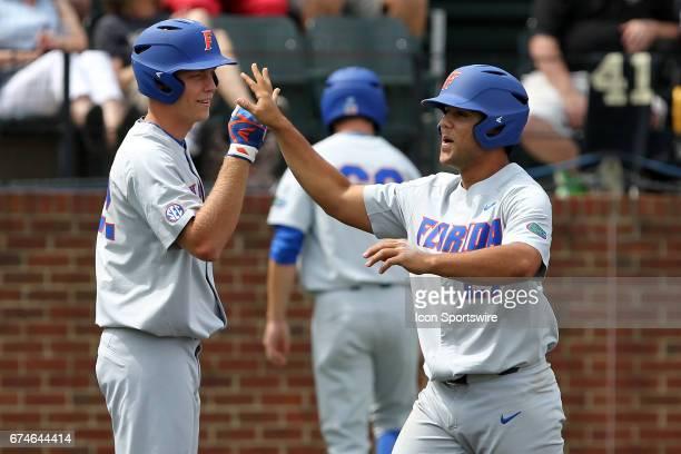 Schwarz of the Gators congratulates Nelson Maldonado after scoring a run during the college baseball game between the Florida Gators and the...