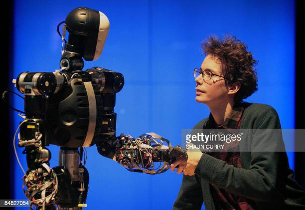 A science museum employee shakes hands with BERTI the robot at the Science Museum in London on February 17 2009 Robot BERTI was developed by UK labs...