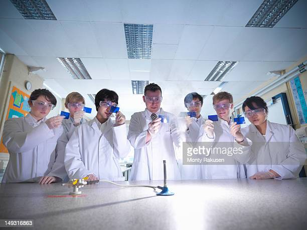 Science teacher and students lighting magnesium in school laboratory