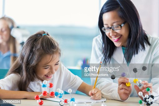 Science teacher helping elementary student study molecule models