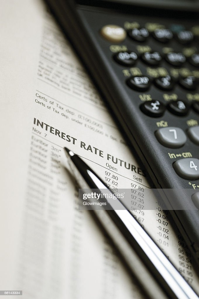 'Scientific calculator, pen and list of interest rates, close-up'