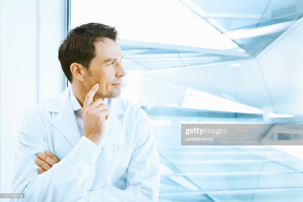 Scientific in labcoat looking through the window : Stock Photo