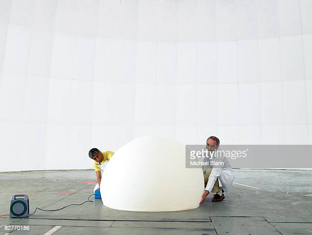 Scientist and engineer inflate weather balloon
