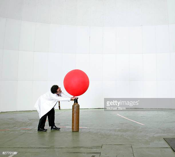Scientist blowing up weather balloon with air