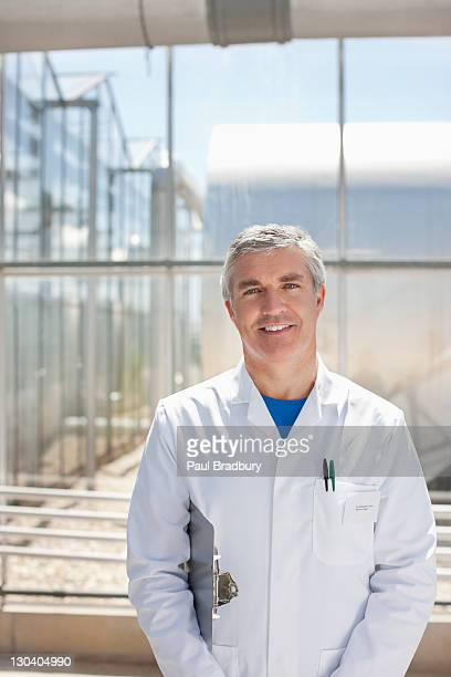 Scientist carrying clipboard in lab