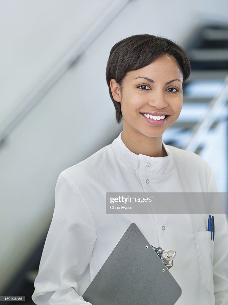 Scientist carrying clipboard in office : Stock Photo