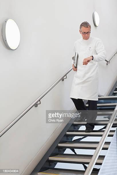 Wissenschaftler überprüfen seine Uhr auf der Treppe