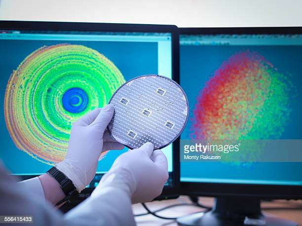 Scientist checking test map of silicon wafer in laboratory, close up