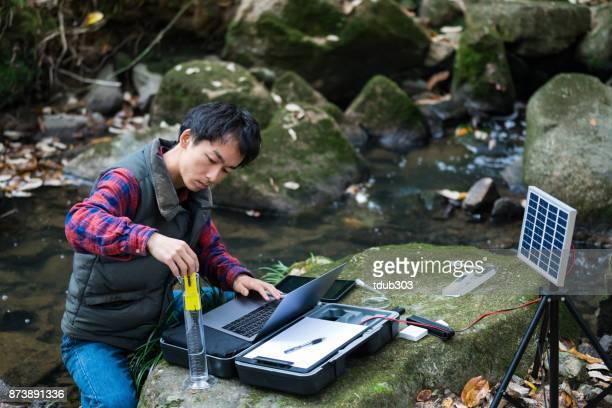 Een wetenschapper verzamelen van gegevens over de kwaliteit van het water van een rivier in het bos