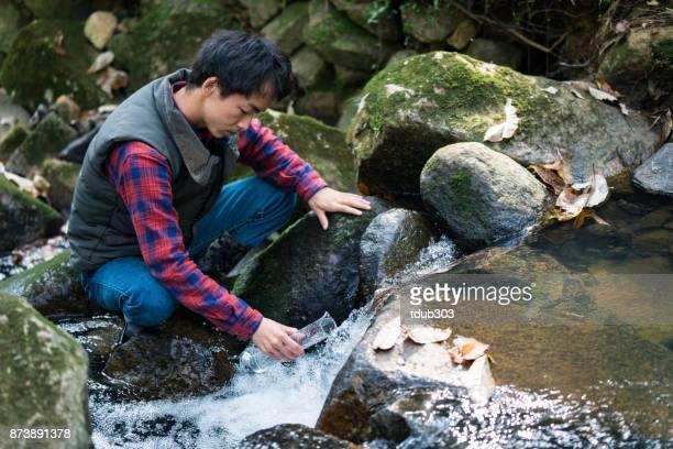 Een wetenschapper die het verzamelen van watermonsters van een rivier in het bos