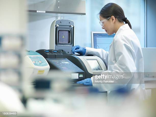 Scientist conducting the process of Polymerase chain reaction (PCR) to amplify DNA by using a thermocycler to create samples