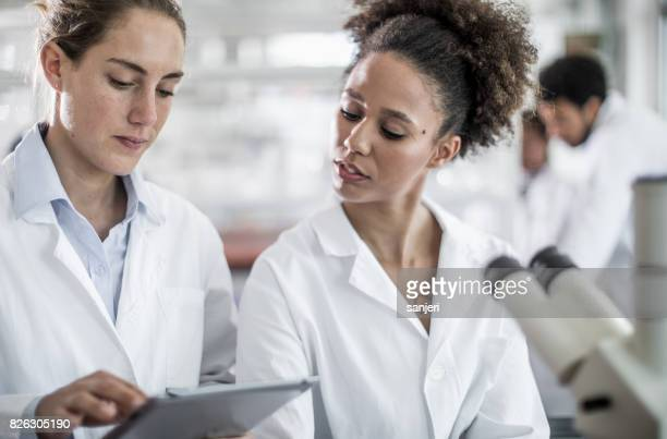 Scientist Discussing in Laboratory, Using Tablet