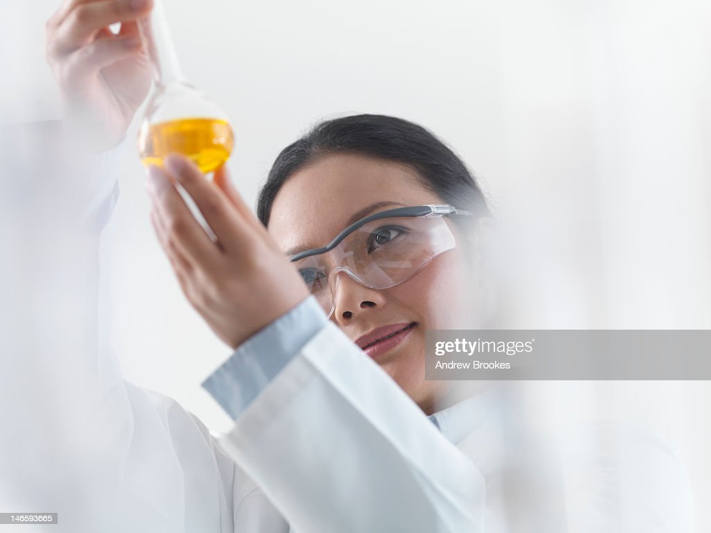 Scientist examining chemicals in lab : Stock Photo