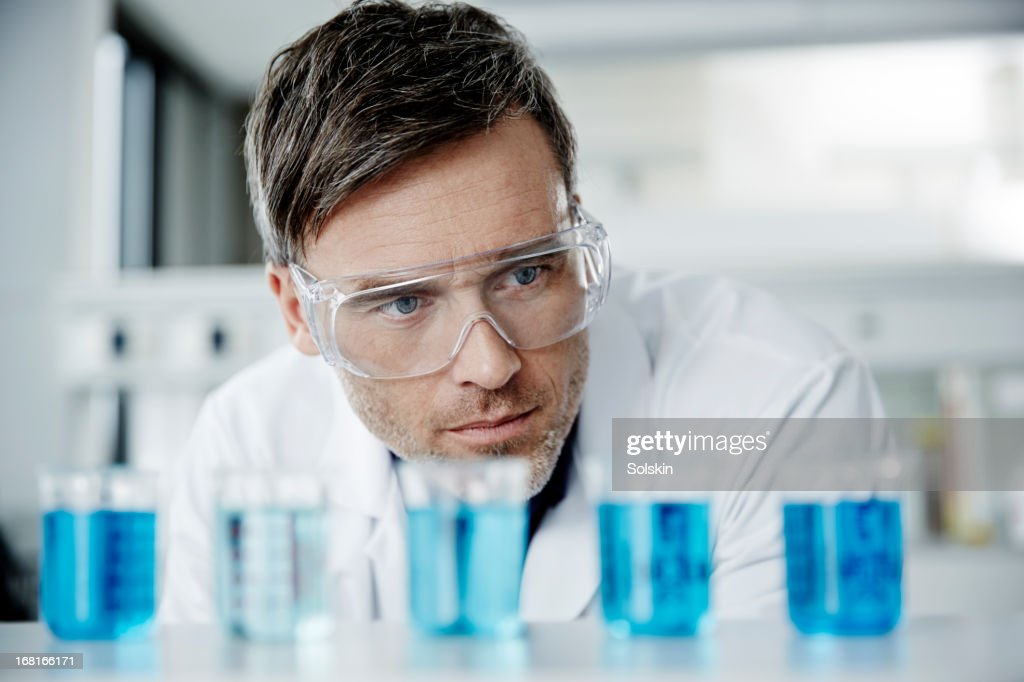 Scientist examining glass beakers : Stock Photo