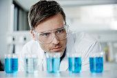 Scientist examining glass beakers