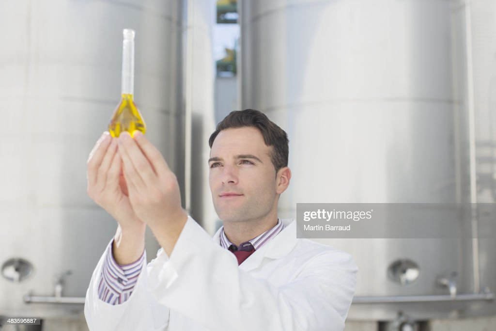 Scientist examining liquid in beaker next to silage storage towers