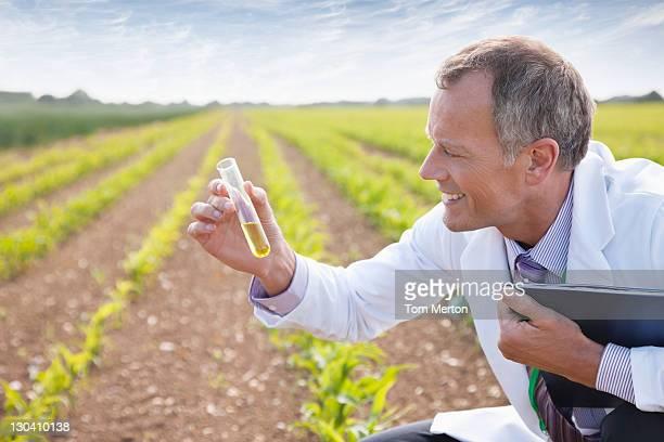 Scientist examining liquid in test tube outdoors