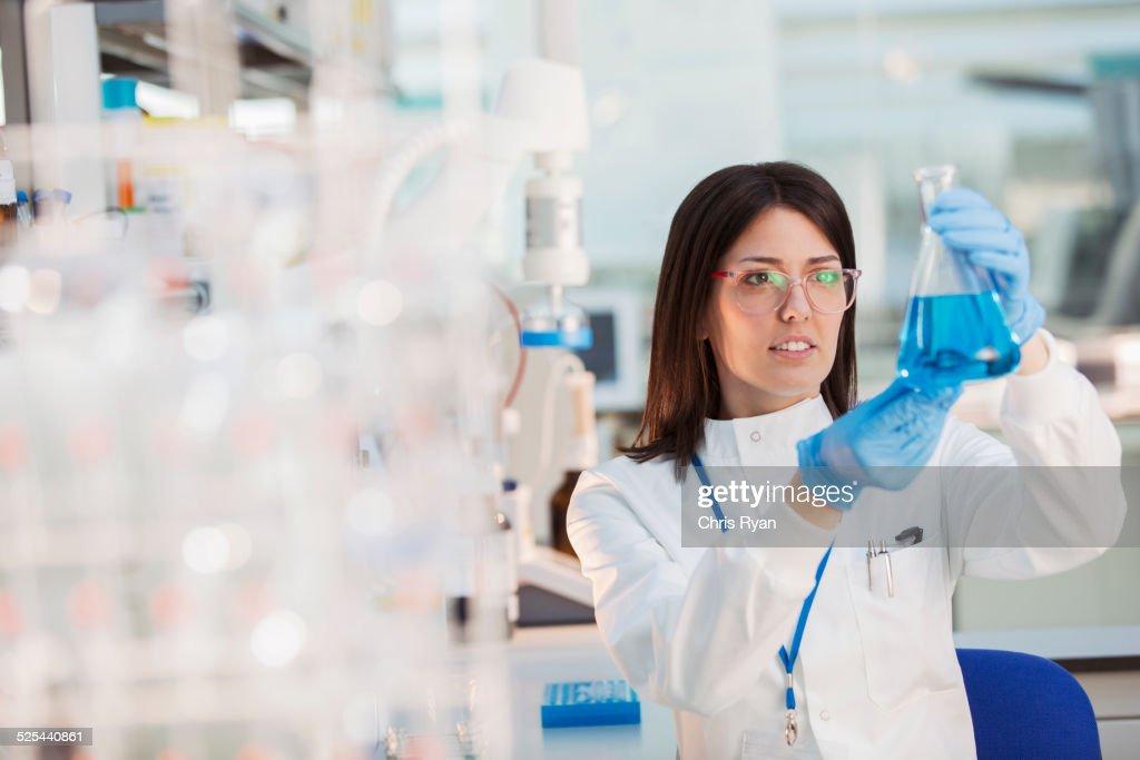 Scientist examining sample in beaker in laboratory : Stock Photo