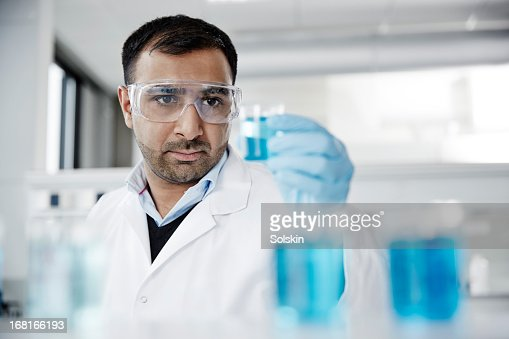 Scientist examining samples in glass beakers : Stock Photo