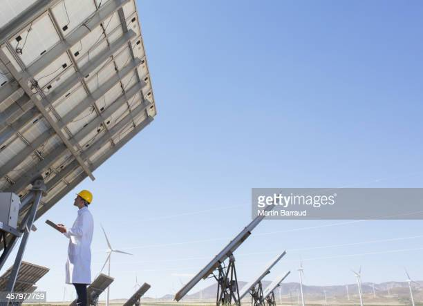 Scientist examining solar panel in rural landscape