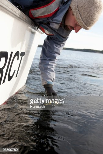 Scientist filling water sample in whirl pak : Stock Photo