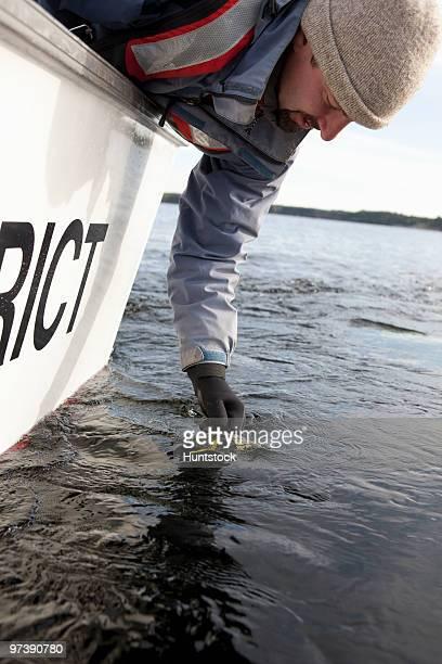 Scientist filling water sample in whirl pak