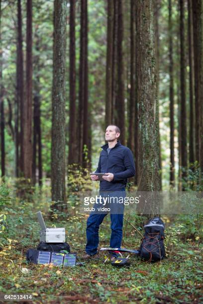 Scientist gathering data in forest with solar powered field station.