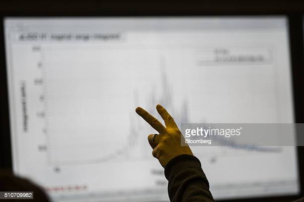 A scientist gestures toward data displayed on screens in the control room of the Laser Interferometer GravitationalWave Observatory at the Hanford...