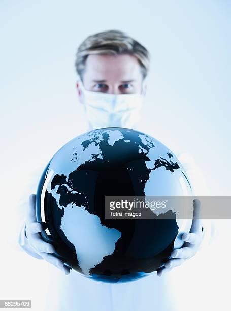 Scientist holding black and white globe