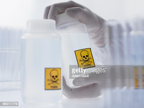 Scientist holding bottle with toxic label