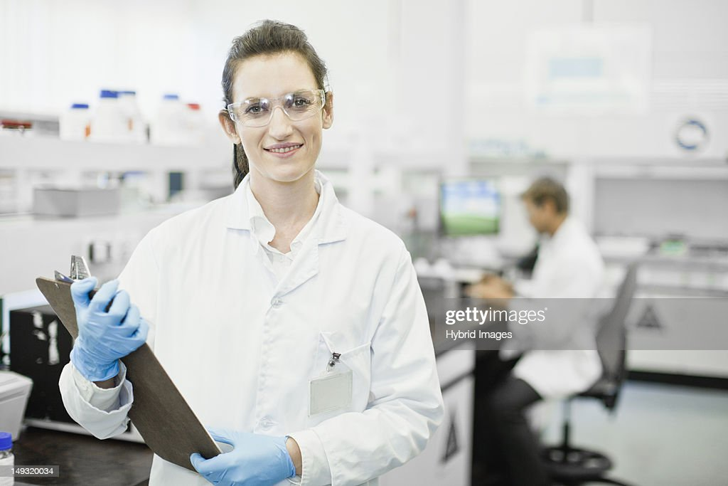 Scientist holding clipboard in lab : Stock Photo