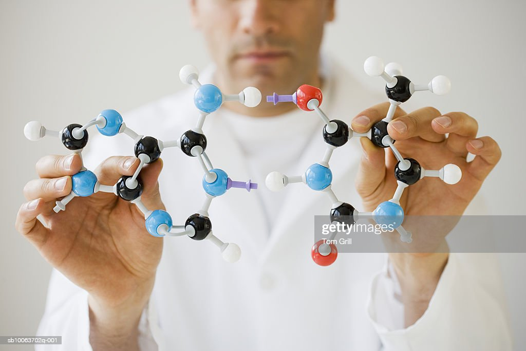 Scientist holding molecule model, mid section, focus on foreground : Stock Photo