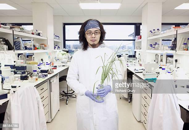 Scientist holding plant in bioscience laboratory