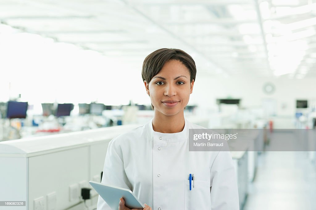 Scientist holding tablet computer in lab : Stock Photo