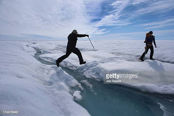Scientist Ian Joughin of the University of Washington leaps over a small meltwater stream as he walks with Graduate Student Laura Stevens from the...