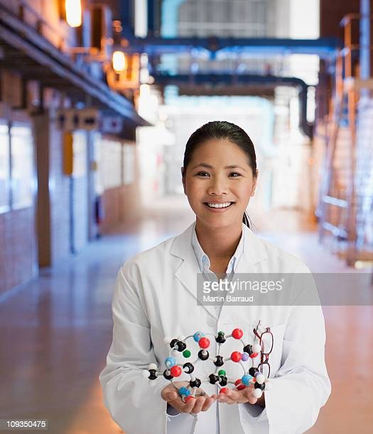 Scientist in factory holding molecule model
