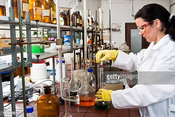 Scientist in lab coat working with chemicals