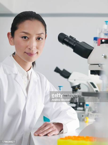 Scientist in laboratory next to microscope, portrait
