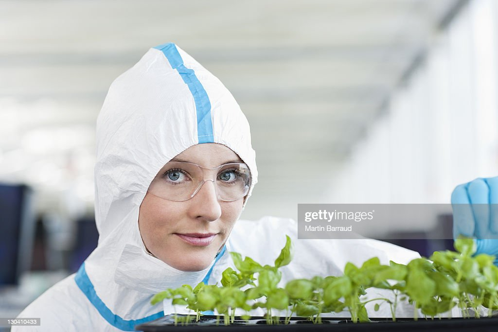 Scientist in protective gear examining plants in lab : Stock Photo