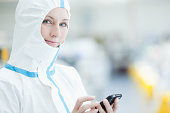 Scientist in protective gear using cell phone