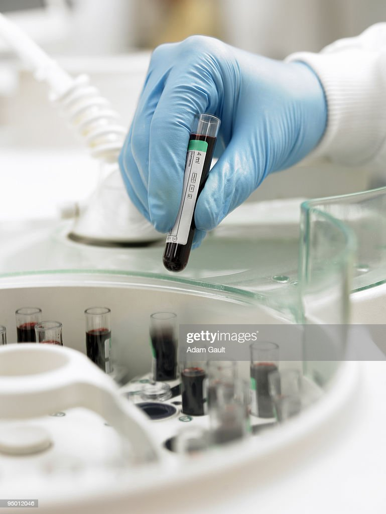 Scientist inserting test tube into centrifuge : Stock Photo