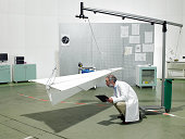 Scientist inspecting paper plane in laboratory
