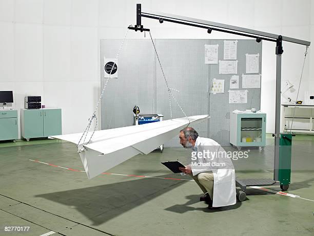 Científico inspeccionar avión de papel en los análisis de laboratorio