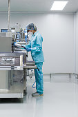 scientist in med suit working with machine